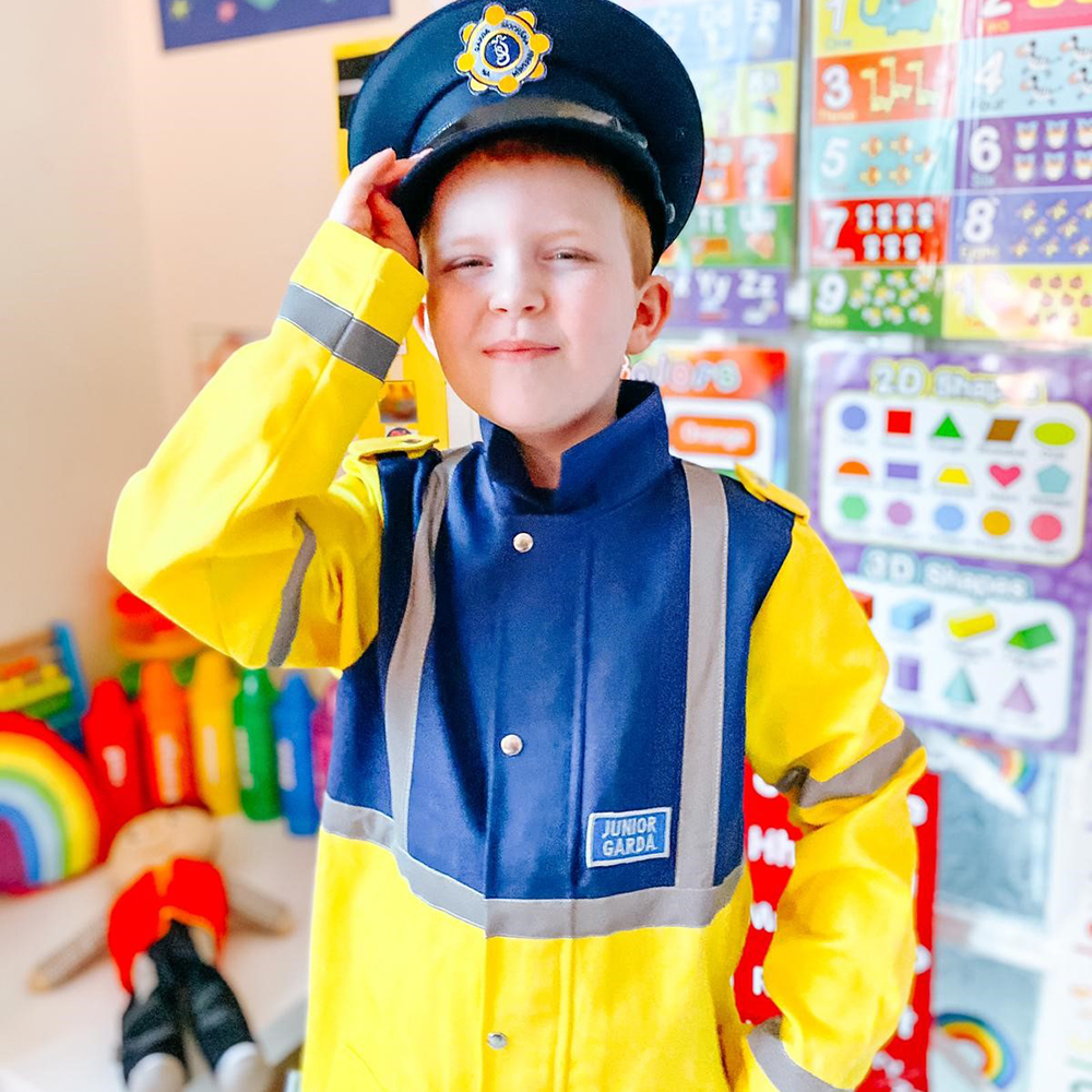 A little boy is smiling and saluting to the camera whilst wearing a junior Garda Síochána costume
