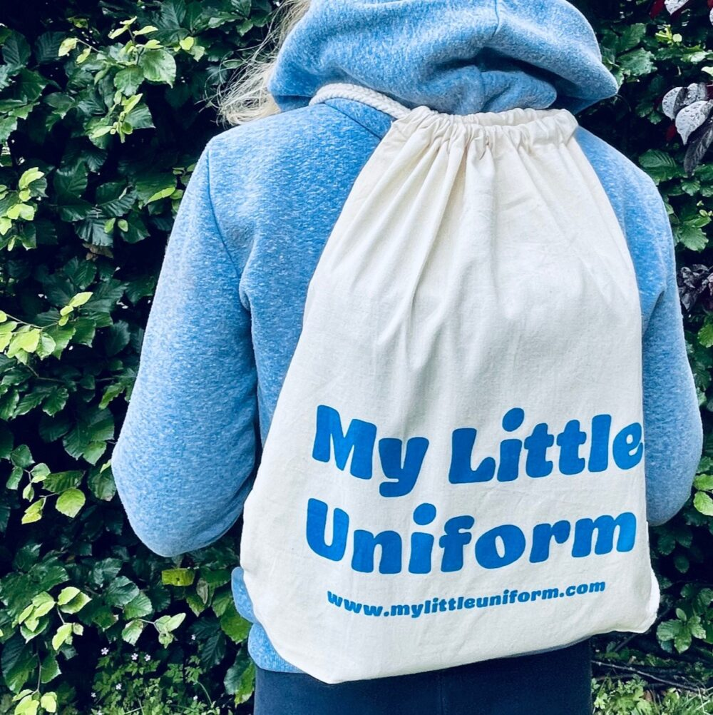 a child wearing a branded cotton drawstring backpack with My Little Uniform printed in blue lettering